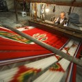 A craftsman works the handloom to weave and create a vibrant patterned silk in Yazd