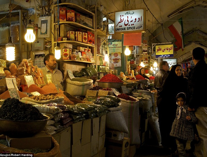 Inside the galleries of the Great Bazaar of Isfahan, with sellers displaying their colourful goods for passers-by