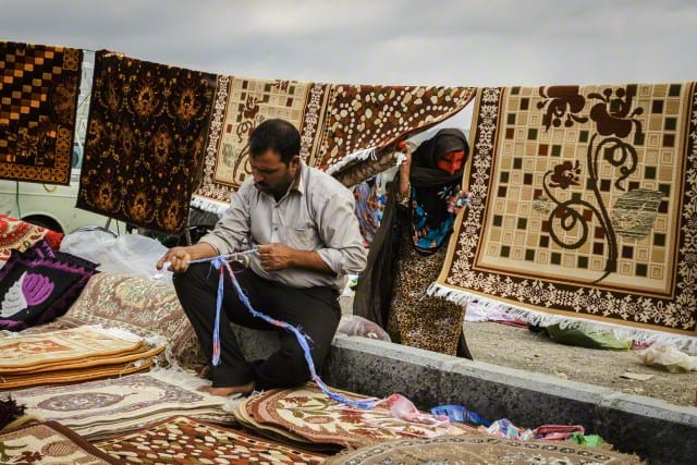 Bandari woman and carpet seller in the weekly 'Panjshambe Bazar', Minab, Iran.