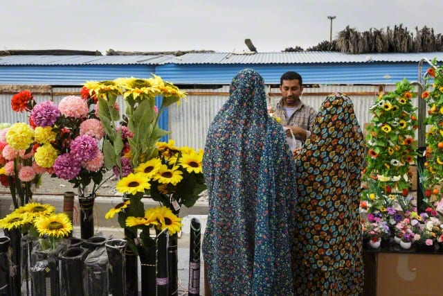 Vendor and women in bright Hijab at the Thursday market or 'Panjshambe Bazar', Minab, Southern Iran