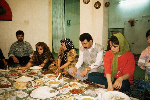 April 1997, Iran --- An Iranian family eats a meal in typical fashion. A carpet is spread onto the floor, the mother and father sit in the middle and the women serve the food. Shiraj, Iran | Location: Shiraj, Iran. --- Image by © Earl & Nazima Kowall/CORBIS