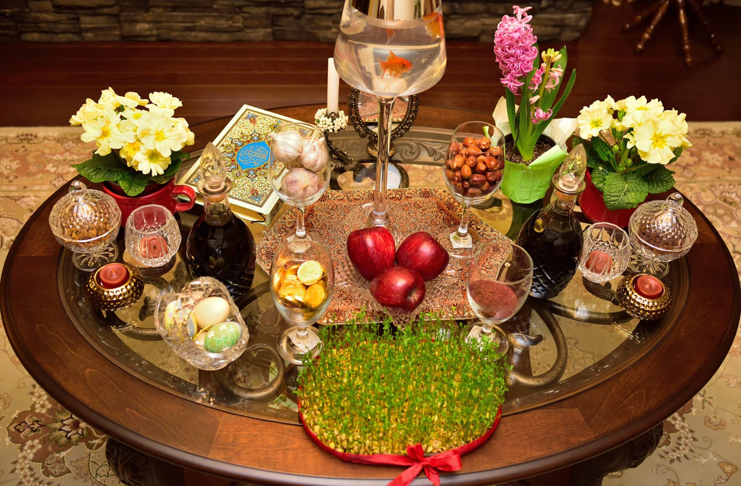 The traditional New Year's spread (sofre-ye haft sin) features seven items that begin with the letter S: sabzeh (sprouts), samanu (pudding), sib (apple), serkeh (vinegar), sir (garlic), senjed (dried oleaster), and somaq (a fruity spice). The spread also typically includes other items such as a copy of the Qur'an, a mirror, and live goldfish. The Iranian New Year, Noruz, is the most important festival of the year and is celebrated by peoples from the Balkans to Central Asia and India.